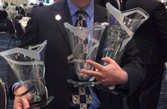 Dr. Erik Chang holding three trophies