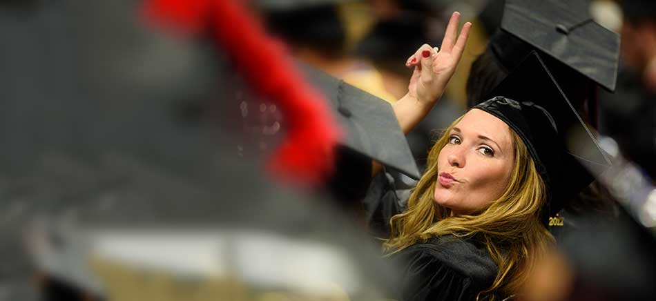 A graduate waves at her family in the stands