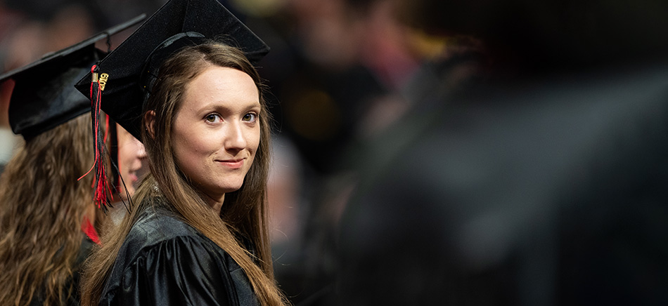 A graduate looks back at the camera during the 2019 Summer Commencement