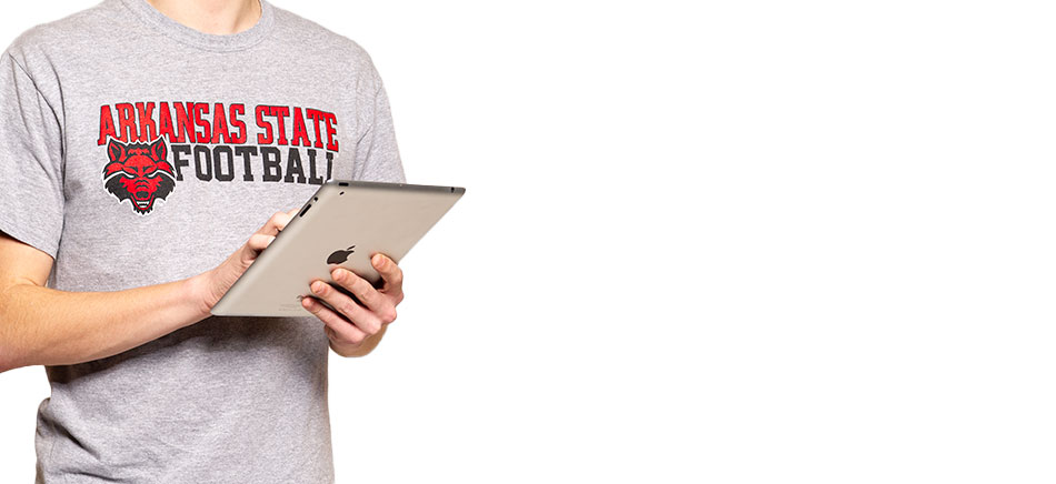 A student holding an iPad in an A-State shirt
