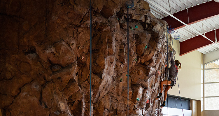 A student climbing the rock wall in the Red WOLF Center