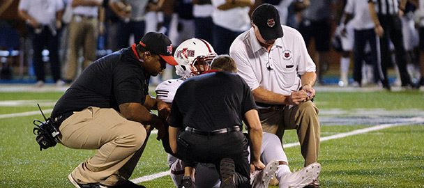 Athletic trainers attending to an injured football player