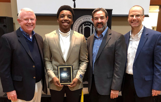 Joseph Branch (second from left) is congratulated on his internship award by Hytrol officials David Peacock, president, Ed Tanner, manager of process development, and Phillip Poston, director of strategic planning.