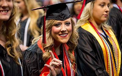 Student at graduation making the redwolf hand sign