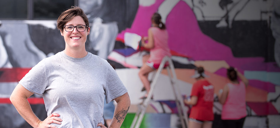 Melissa Wilkinson in front of the mural in downtown Jonesboro