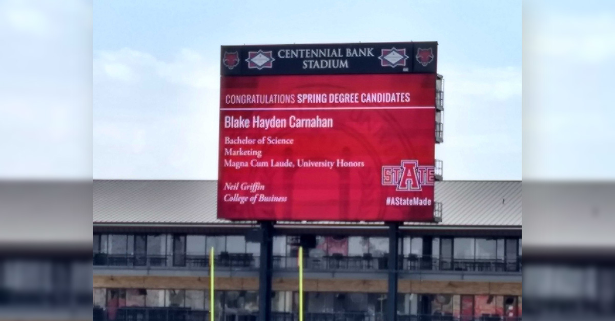 A graduate's information appears on the video board
