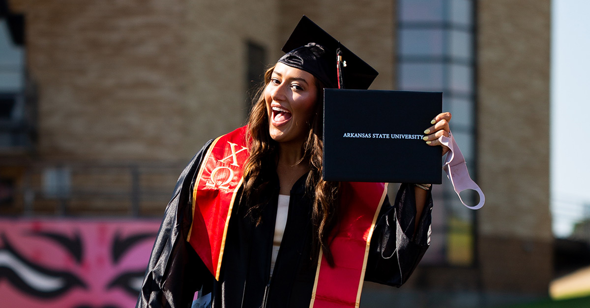 A graduate poses with her diploma cover at our 2020 Spring Commencement