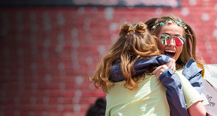 Two sorority members hugging on Bid Day