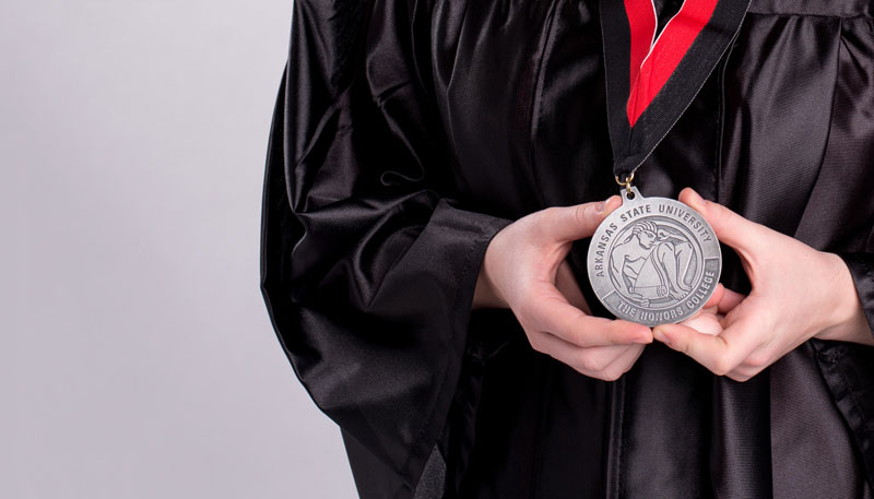 An honors graduate holding a medal
