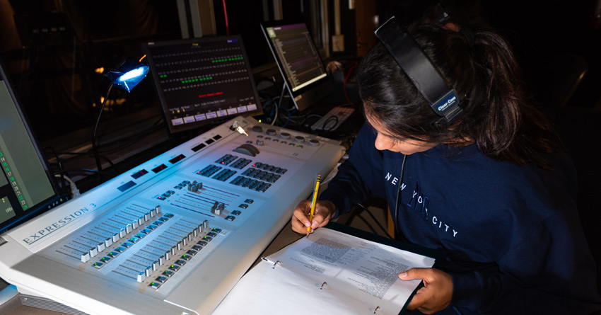 A student taking lighting notes in the booth