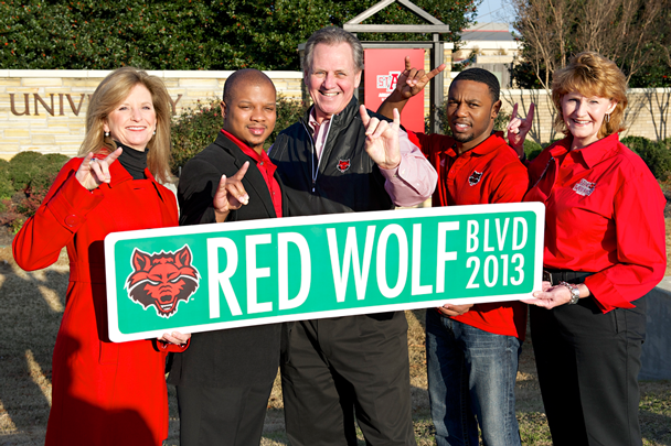 A-State campus leadership holds the Red Wolf Blvd sign in front of Stadium Blvc