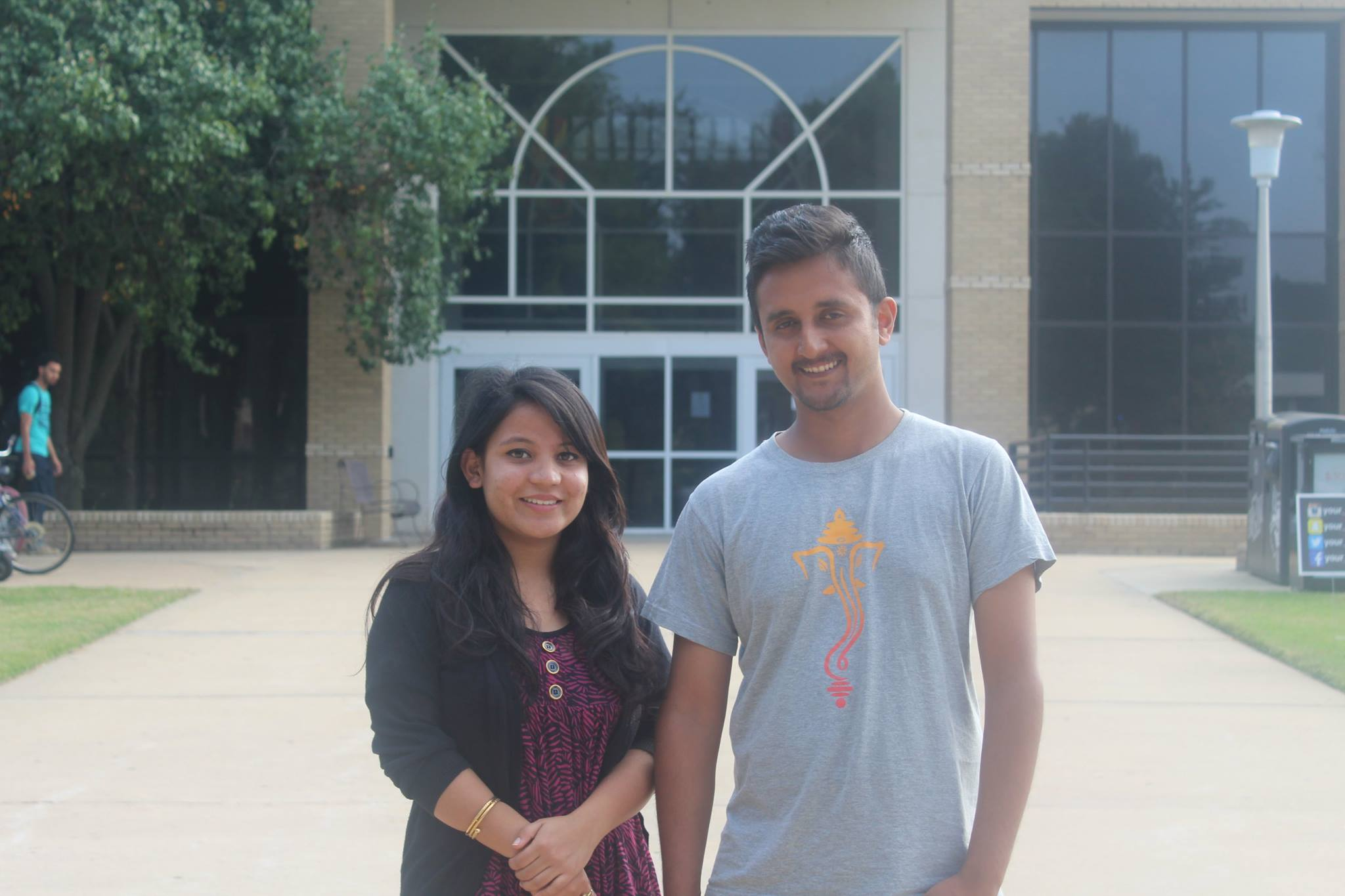 a male and female student standing side by side; both are international