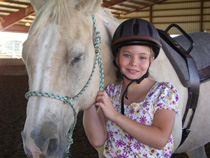 A child posing with a horse at the Equine Center