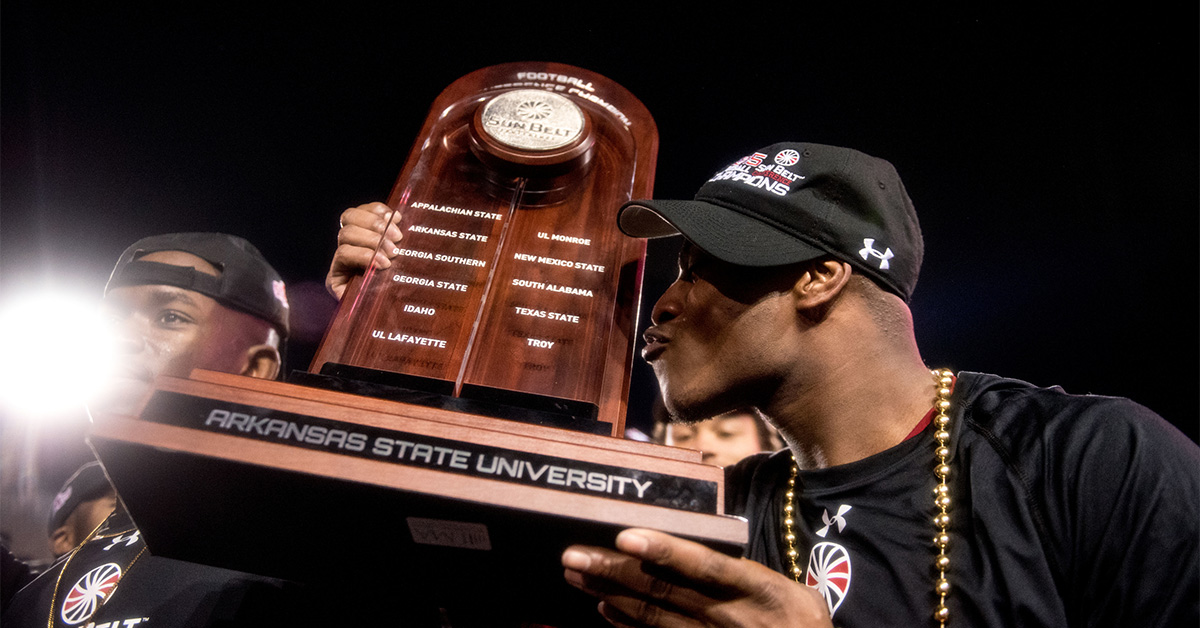 A-State player holding the Sun Belt Trophy