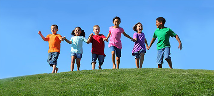 Kids running on grassy hill