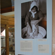 photo of woman scrubbing clothes with scrub board in the Living Off The Land exhibit