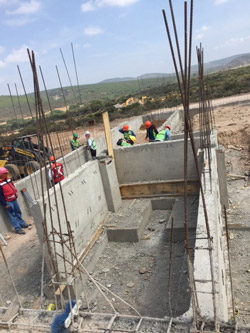 Construction workers at the Arkansas State University Campus Queretaro site in Mexico install concrete footings.