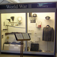 exhibit case with uniforms and guns in the Military Gallery