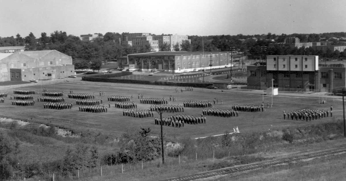 ROTC annual formal inspection (AFI), about 1965, at the drill field where the Health, Physical Education and Sport Sciences Building now stands.  Wilson Hall, Computer Science and Mathematics Building and Arkansas Hall  are among the buildings in the background.