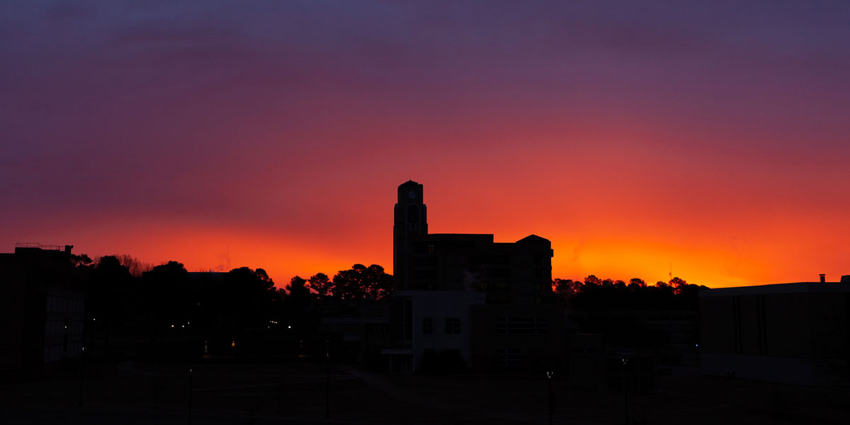 The sun rising over the Dean B. Ellis Clocktower